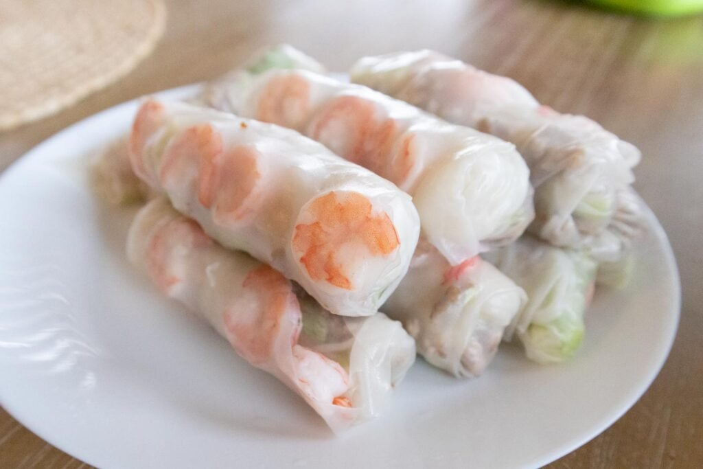 making Vietnamese summer rolls with ground pork and shrimp on plate